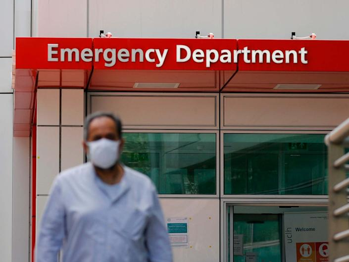 A man wearing a mask is seen walking outside the entrance to the emergency department of University College Hospital: AFP via Getty Images