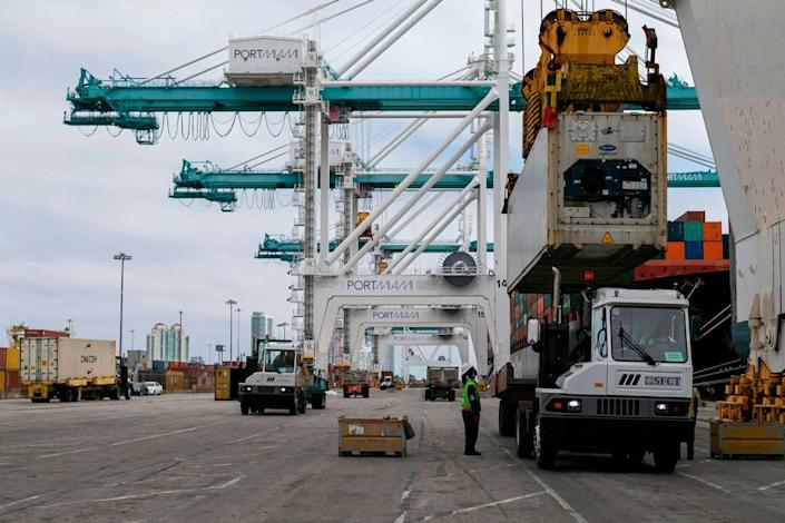 Longshoremen work to offload containers from a cargo ship at PortMiami on Saturday, February 20, 2021.