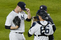 New York Yankees catcher Kyle Higashioka (66) and pitching coach Matt Blake, (behind the catcher) confer with Yankees relief pitcher Lucas Luetge, right, during a mound visit in the ninth inning of a baseball game against the Baltimore Orioles, Tuesday, April 6, 2021, at Yankee Stadium in New York. Luetge allowed a two-run, home run to Baltimore Orioles Rio Ruiz, but closed out the game in the Yankees 7-2 victory over Baltimore. (AP Photo/Kathy Willens)
