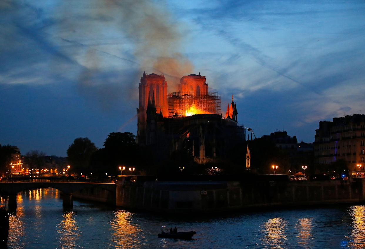 Plumes of yellow brown smoke fill the air above Notre Dame Cathedral. (Photo: Michel Euler/AP)