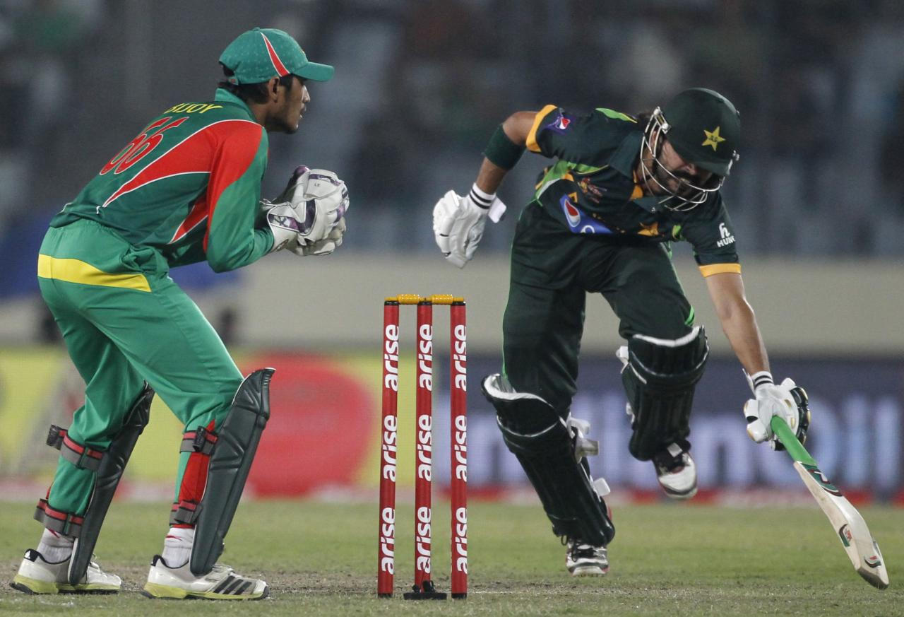 Pakistan's Fawad Alam (R) avoids a run out as Bangladesh's wicketkeeper Anamul Haque attempts to catch the ball during their one-day international (ODI) cricket match in Asia Cup 2014 in Dhaka March 4, 2014. REUTERS/Andrew Biraj (BANGLADESH - Tags: SPORT CRICKET)