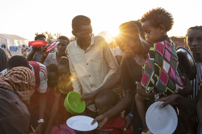 Tigray refugees who fled the conflict in Ethiopia's Tigray region, wait to get cooked rice served by Sudanese local volunteers at Um Rakuba refugee camp in Qadarif, eastern Sudan, Monday, Nov. 23, 2020. Tens of thousands of people have fled a conflict in Ethiopia for Sudan, sometimes so quickly they had to leave family behind. There is not enough to feed them in the remote area of southern Sudan that they rushed to. (AP Photo/Nariman El-Mofty)