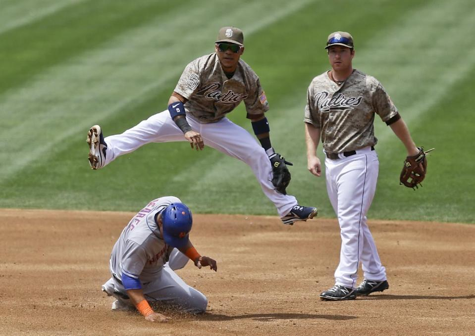 San Diego Padres shortstop Alexi Amarista, top left, hurdles New York Mets' Juan Lagares while relaying to first to get Travis d'Arnaud out for a double play in the second inning of a baseball game on Sunday, Aug. 18, 2013, in San Diego. Padres second baseman Jedd Gyorko, right, looks on. (AP Photo/Lenny Ignelzi)
