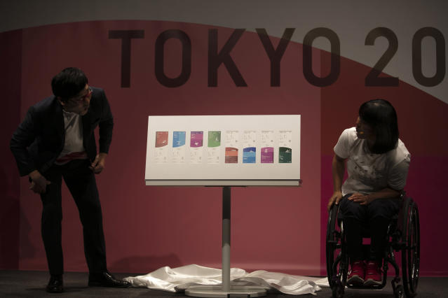 Paralympian Monika Seryu, right, and comedian Ryota Yamasato look at tickets for the Tokyo 2020 Olympics and Paralympics Wednesday, Jan. 15, 2020, in Tokyo. (AP Photo/Jae C. Hong)