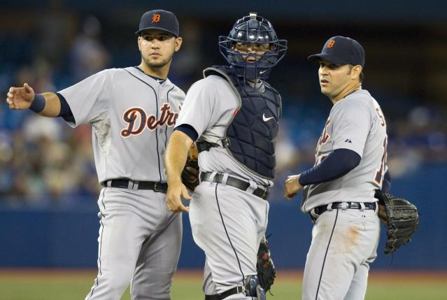 Detroit Tigers catcher Alex Avila and Nick Castellanos signal to the trainer for pitcher Anibal Sanchez, right, during the fifth inning of a baseball game, Friday, Aug. 8, 2014 in Toronto. (AP Photo/The Canadian Press, Fred Thornhill)