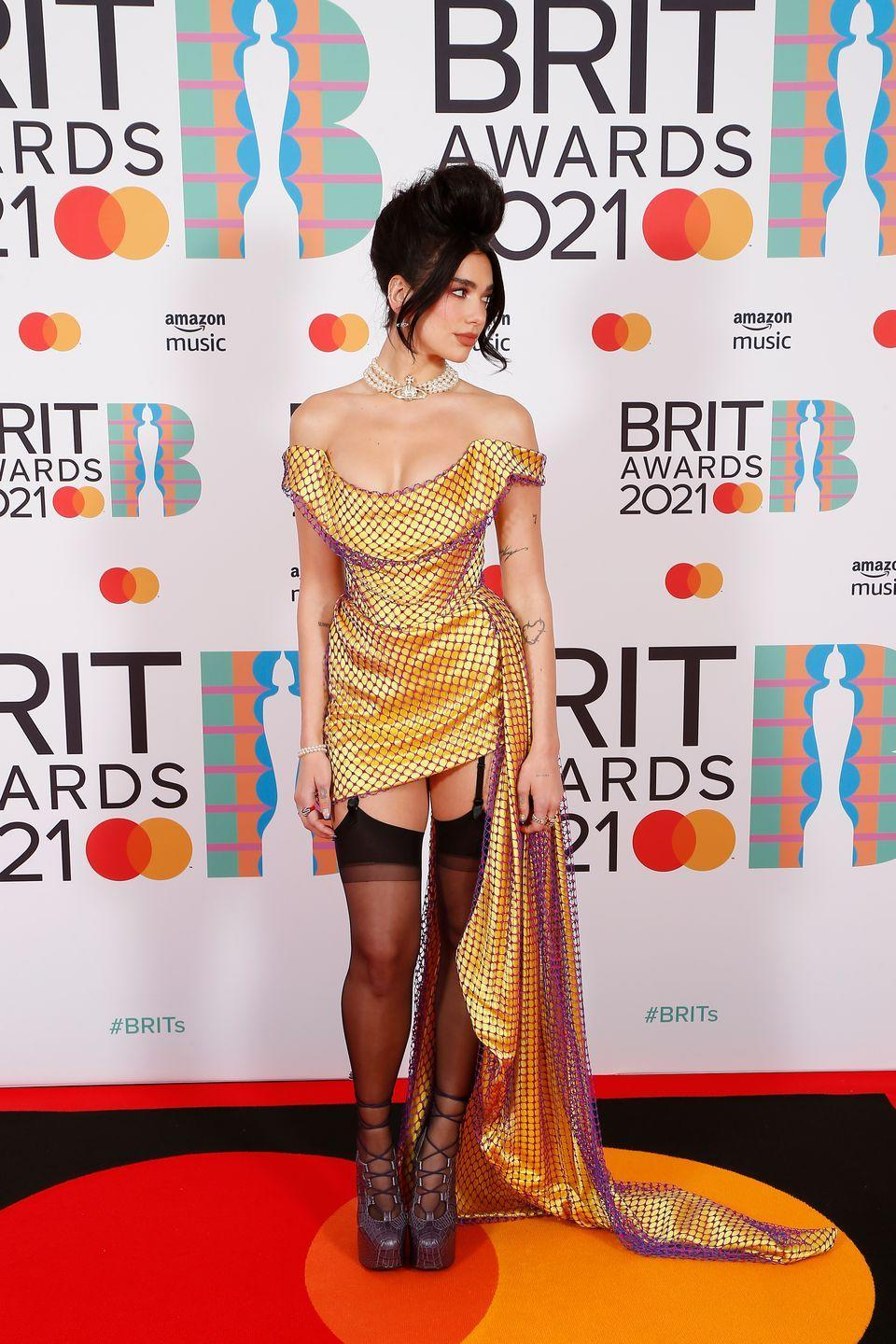 <p>Dua Lipa embraced Vivienne Westwood's trademark corset silhouette for the occasion. The singer teamed the off-the-shoulder mini dress with suspender stockings and lace-up platforms.</p>