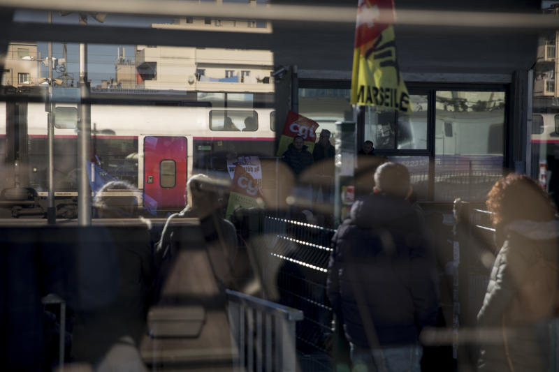 Railway workers are pictured in the reflection of a train window as they gather for a union general assembly meeting at the Gare St-Charles station in Marseille, southern France, Monday, Dec. 9, 2019. Paris commuters inched to work Monday through exceptional traffic jams, as strikes to preserve retirement rights halted trains and subways for a fifth straight day. (AP Photo/Daniel Cole)