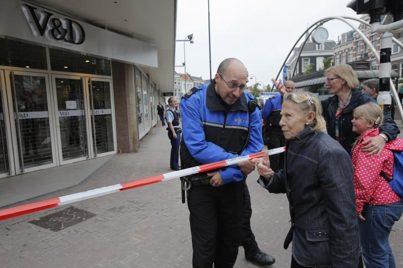 """Bystanders talk to police officers guarding the entrance to a closed store in Haarlem, western Netherlands, Wednesday Sept. 25, 2013. Three stores in the Dutch city of Haarlem have been closed after threats of an attack were made from an anonymous Twitter account. Haarlem police said in a statement Tuesday that they are taking the threats """"seriously"""" and they are trying to identify the person behind the account, which has been suspended. (AP Photo/Peter Dejong)"""