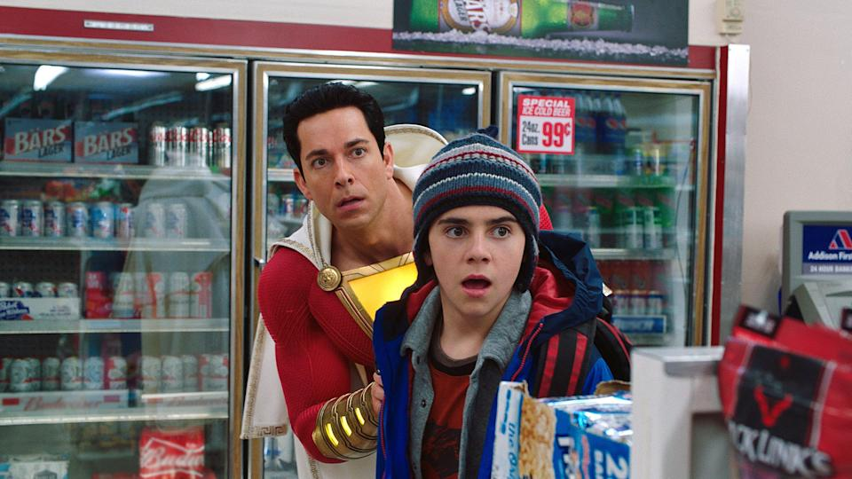 """Super-sized Billy Batson (Zachary Levi, left) and Freddy Freeman (Jack Dylan Grazer) run into robbers on a mission to buy beer in """"Shazam!"""""""