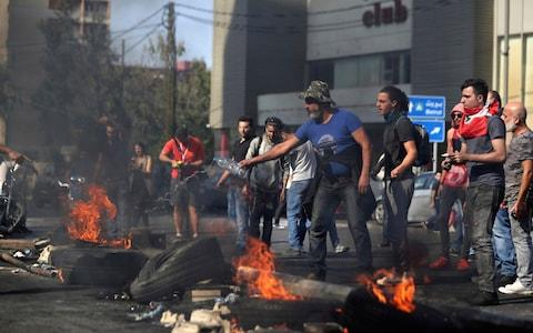 Anti-Government protesters set fire to tires blocking a road in the town of Jal el-Dib - Credit: AP Photo/Bilal Hussein