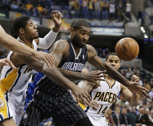 Orlando Magic's Kyle O'Quinn, center, works next to Indiana Pacers' Paul George (24) during the first half of an NBA basketball game Tuesday, March 19, 2013, in Indianapolis. (AP Photo/Darron Cummings)