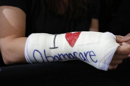 """Park of Cambridge wears cast for her broken wrist with """"I Love Obamacare"""" written upon it prior to U.S. President Barack Obama's arrival to speak about health insurance at Faneuil Hall in Boston"""