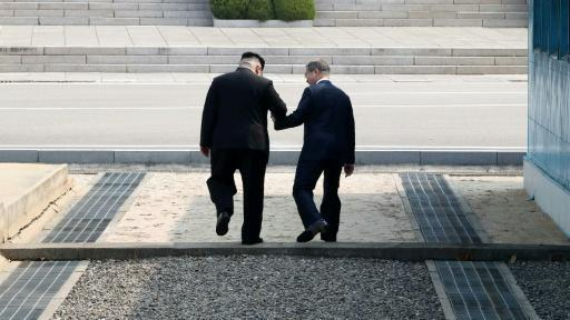 North Korea's leader Kim Jong Un and South Korea's President Moon Jae-in hold hands as they step together over the Military Demarcation Line that divides their countries at Panmunjom