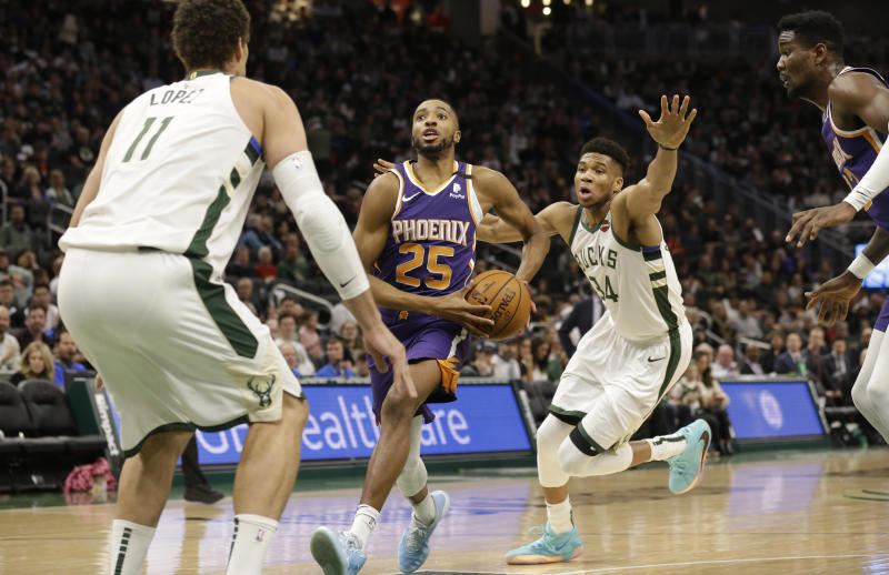 Phoenix Suns' Mikal Bridges (25) drives against Milwaukee Bucks' Brook Lopez (11) during the second half of an NBA basketball game Sunday, Feb. 2, 2020, in Milwaukee. (AP Photo/Jeffrey Phelps)