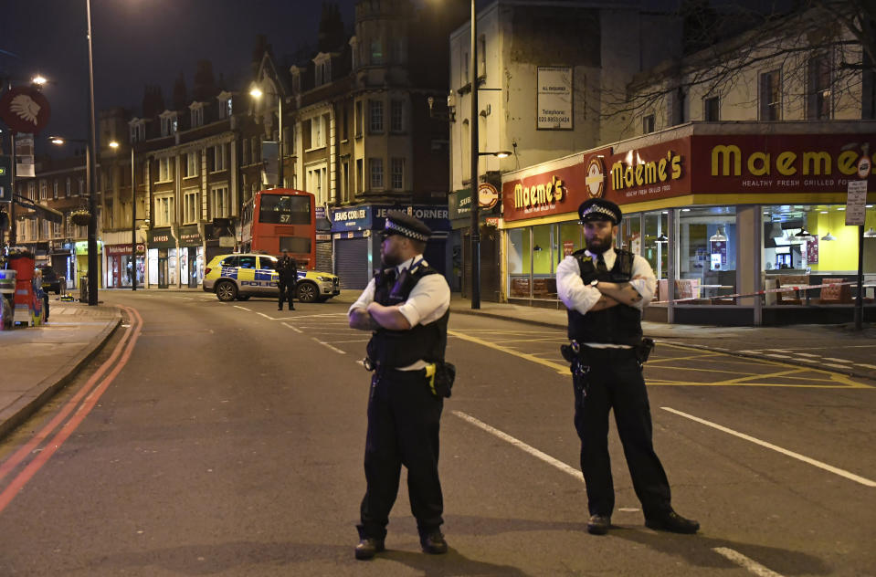 Police officers stand guard near the scene after a stabbing incident in Streatham London, England, Sunday, Feb. 2, 2020. London police officers shot and killed a suspect after at least two people were stabbed Sunday in what authorities are investigating as a terror attack. (AP Photo/Alberto Pezzali)
