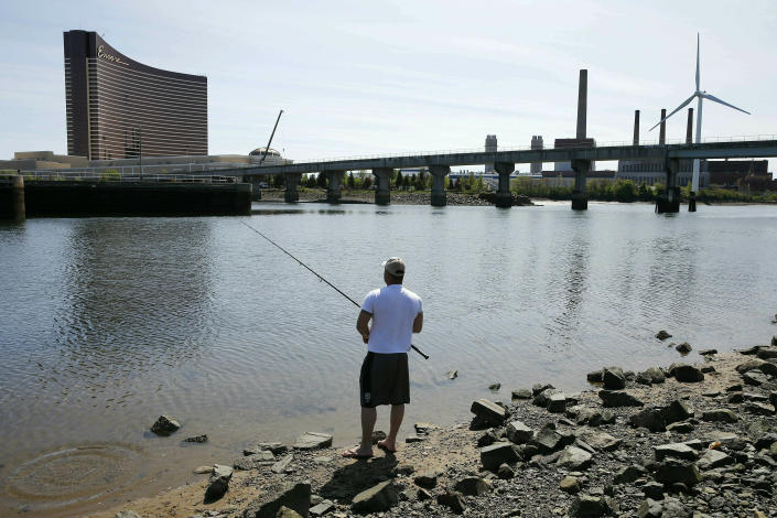 FILE - In this May 22, 2019 file photo, a man fishes in the Mystic River in Somerville, Mass., across from the Encore Boston Harbor in Everett, Mass. The casino is scheduled to open on Sunday, June 23. (AP Photo/Michael Dwyer, File)