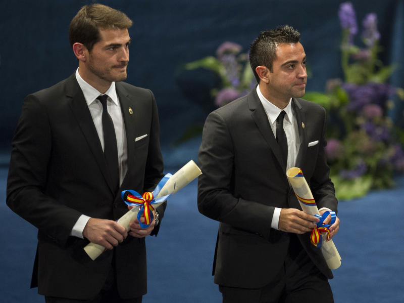 Prince of Asturias prize winners for Sports, Real Madrid soccer player Iker Casillas, left, and FC Barcelona soccer player Xavi Hernandez, right, hold their prizes during an awards ceremony in Oviedo, Spain, Friday Oct. 26, 2012. The award is one of eight of Spain's prestigious Asturias prizes, presented by Spanish Crown Prince Felipe and granted each year in various categories. (AP Photo/Juan Manuel Serrano Arce)