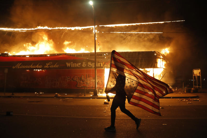 A protester carries a US flag upside down in front of burning building.