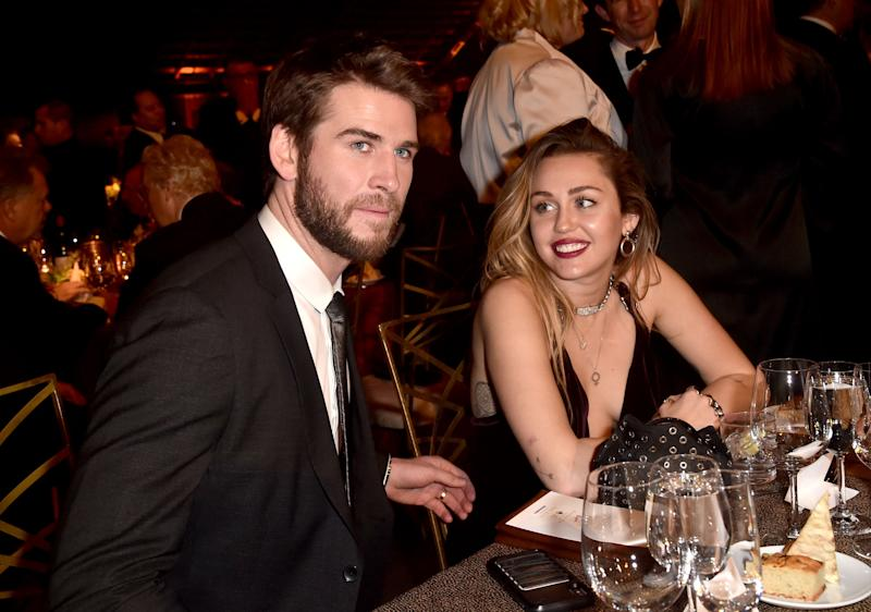 Miley Cyrus and Liam Hemsworth at a table