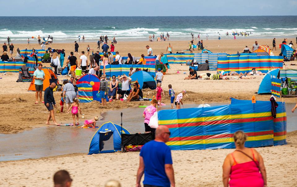 "Tourists flocks to the Perranporth beach in Cornwall. 1st August 2020. See SWNS story SWPLtourism; Cornwall residents fear a local lockdown and say they are ""scared to leave their houses""  - as some of the county's beaches are likened to ""Benidorm on steroids"". Some of the more popular seaside destinations along the south-west coast have seen trails of cars queuing through the town as visitors flock to beaches or holiday parks in search of a 'staycation'. But locals in these popular towns have been left feeling ""uneasy"" about leaving their homes - and some fear they could be in for a local lockdown set to be worse than the first lockdown. Tina-Marie Lally, from Penzance, tried to visit Porthminster Beach in St Ives last week - but shared photos on Facebook of the beach crowded with people and windbreakers."