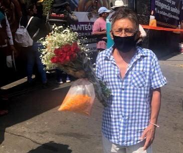 A man in a mask holds flowers