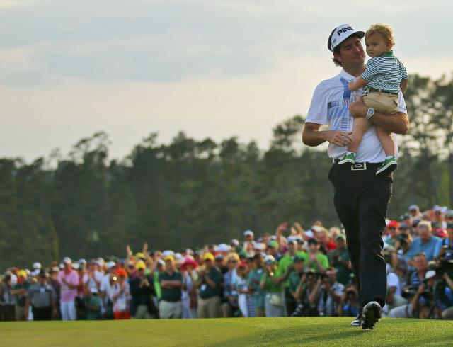 U.S. golfer Bubba Watson celebrates after winning the tournament on the 18th green with his son Caleb during the final round of the Masters golf tournament at the Augusta National Golf Club in Augusta, Georgia April 13, 2014. REUTERS/Brian Snyder (UNITED STATES - Tags: SPORT GOLF)