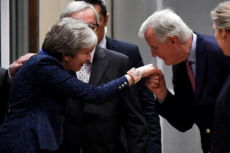 Prime Minister Theresa May is greeted by the EU's chief negotiator Michel Barnier on Saturday night (EPA)