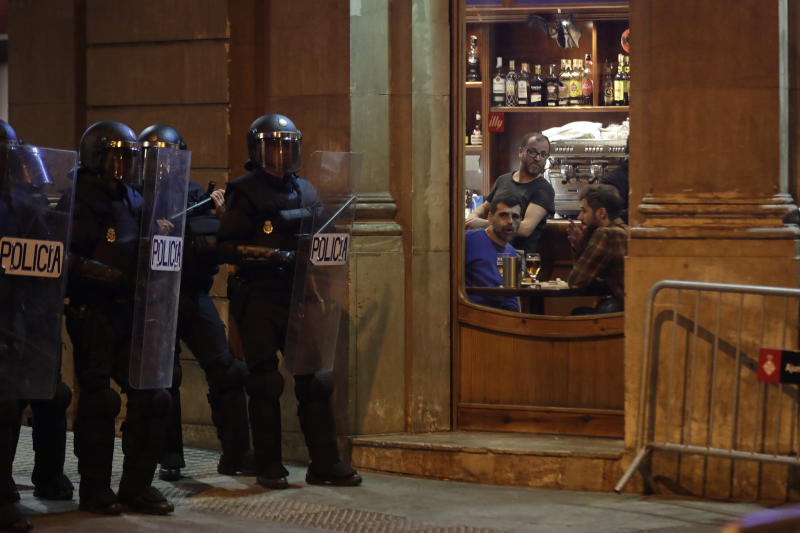 People sitting in a bar look at a line of policemen outside during a pro-independence demonstration in Barcelona, Spain, Sunday, Oct. 20, 2019. Barcelona and the rest of the restive Spanish region of Catalonia are reeling from several days of violent protests for the sentencing of 12 separatist leaders to lengthy prison sentences.Riots have broken out at nightfall following huge peaceful protests each day since Monday's Supreme Court verdict. (AP Photo/Ben Curtis)