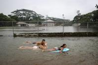 <p>Residents bodyboard in floodwaters at a baseball field during flooding from Tropical Storm Lane on the Big Island on Aug. 25, 2018 in Hilo, Hawaii. (Photo: Mario Tama/Getty Images) </p>