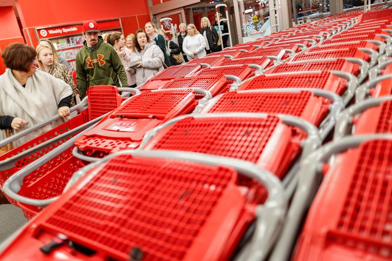 FILE- In this Friday, Nov. 23, 2018, file photo, shoppers enter and take their shopping carts during a Black Friday sale at a Target store in Newport, Ky. On Tuesday, Nov. 27, the Conference Board releases its November index on U.S. consumer confidence. (AP Photo/John Minchillo, File)