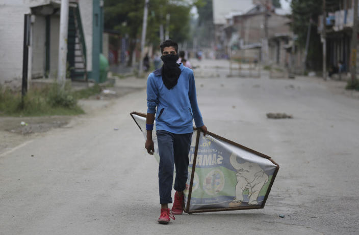 A Kashmiri protester drags an advertisement hoarding to be used as a shield during an anti-India protest Srinagar, India, Friday, Aug. 9, 2019. The predominantly Muslim area has been under an unprecedented security lockdown and near-total communications blackout to prevent unrest and protests after India's Hindu nationalist-led government said Monday it was revoking Kashmir's special constitutional status and downgrading its statehood. (AP Photo/Altaf Qadri)