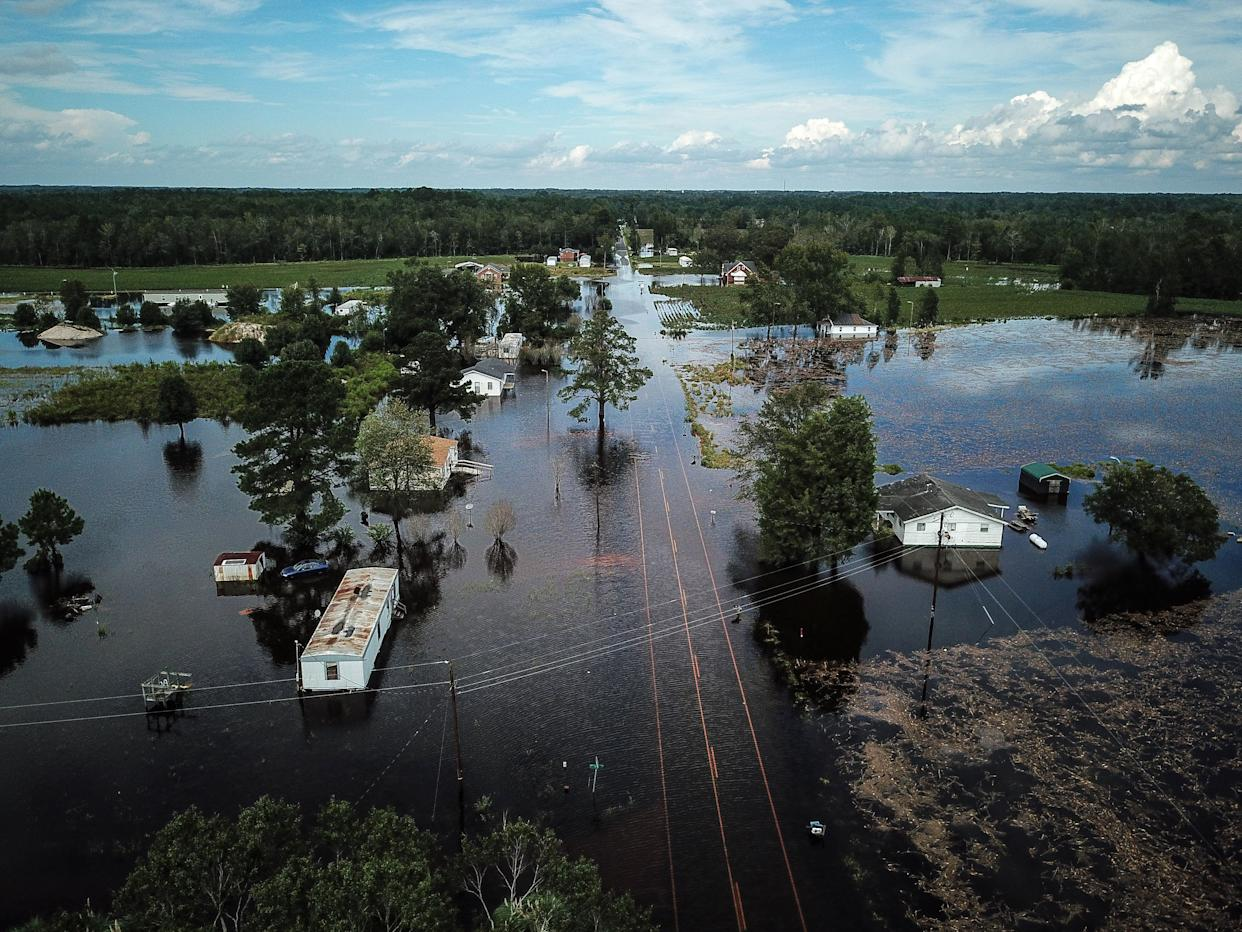 A flooded neighborhood stands next to the Lumber River in Lumberton.
