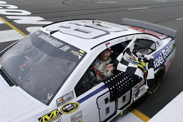 Dale Earnhardt Jr. (88) holds the checkered flag after winning the NASCAR Sprint Cup Series auto race at Pocono Raceway, Sunday, Aug. 3, 2014, Long Pond, Pa. (AP Photo/Mel Evans)