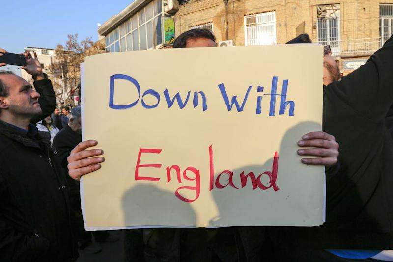 "An Iranian protester holds a ""Down with England"" placard outside the British embassy in Tehran on Sunday (Picture: AFP/Getty)"