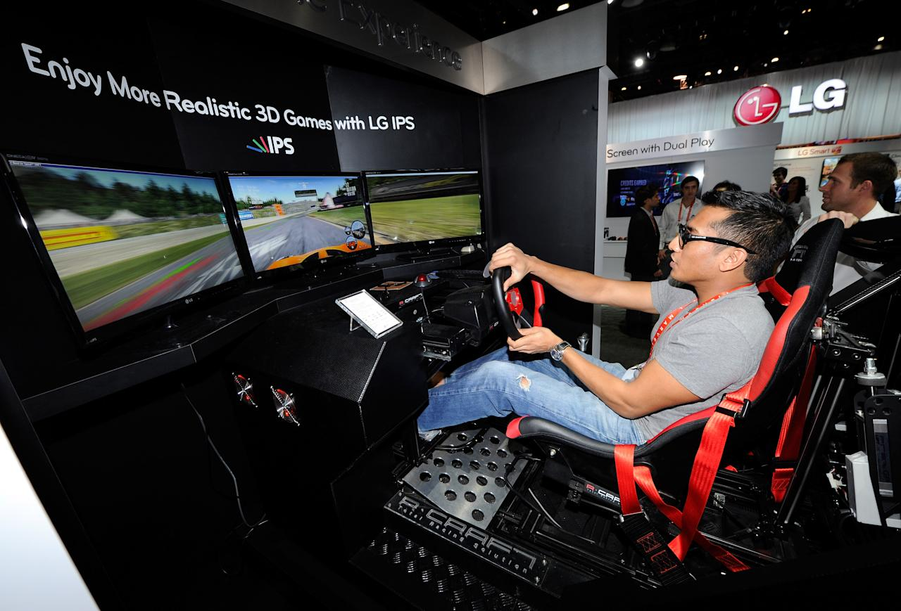 """LAS VEGAS, NV - JANUARY 11:  Sujhon Das of Nevada plays the """"Need for Speed: Shift"""" racing video game using a racing motion machine and LG Cinema 3D IPS TVs at the LG Electronics booth at the 2012 International Consumer Electronics Show at the Las Vegas Convention Center January 11, 2012 in Las Vegas, Nevada. CES, the world's largest annual consumer technology trade show, runs through January 13 and features more than 3,100 exhibitors showing off their latest products and services to about 140,000 attendees.  (Photo by Ethan Miller/Getty Images)"""