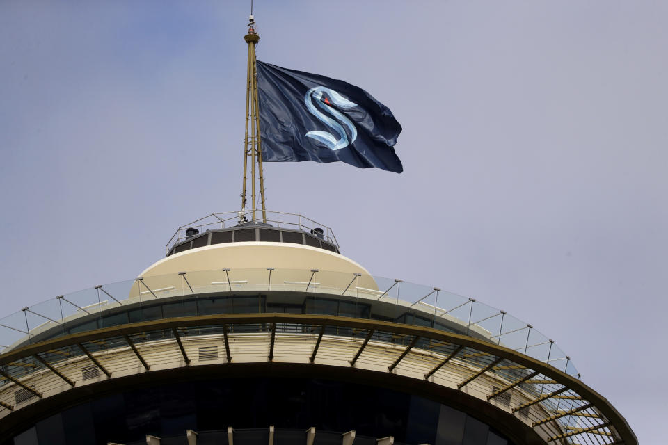 A flag with the new logo for the newly-named Seattle NHL team, the Seattle Kraken, flies atop the iconic Space Needle in Seattle.
