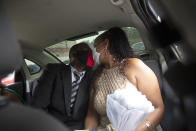 Wearing masks to prevent the spread of the new coronavirus, a couple kisses during their drive-thru wedding at a registry office in the neighborhood of Santa Cruz in Rio de Janeiro, Brazil, Thursday, May 28, 2020. Couples unable to have a traditional wedding because of the coronavirus pandemic are now taking part in drive-thru weddings. (AP Photo/Silvia Izquierdo)
