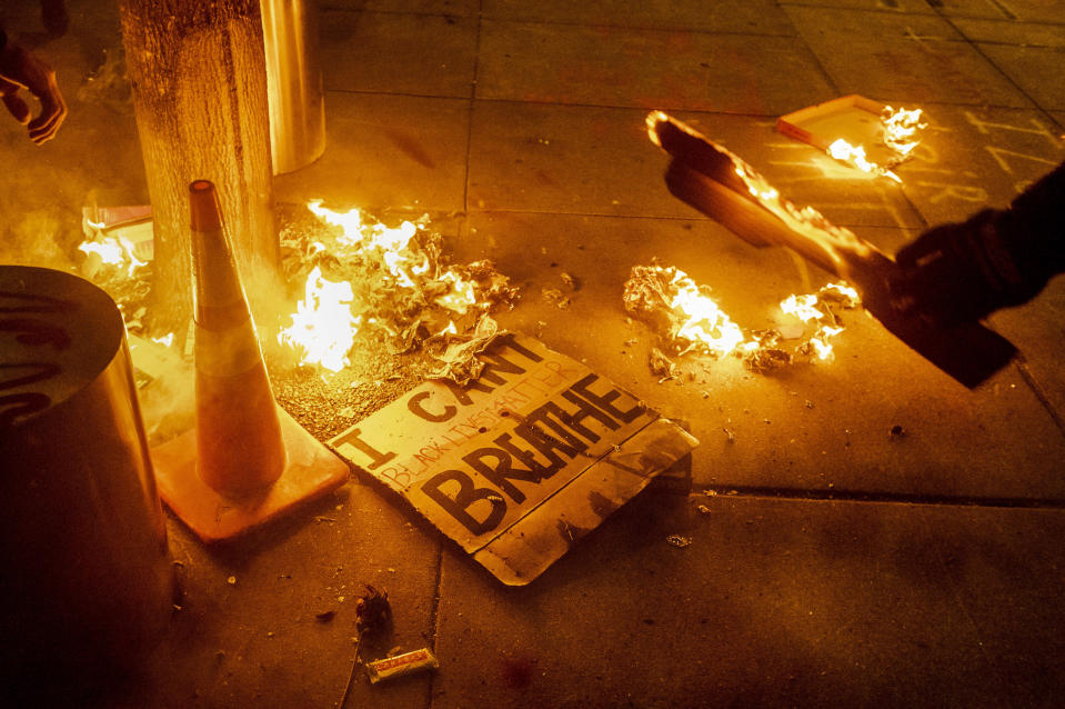 A Black Lives Matter protester burns a sign outside the Mark O. Hatfield United States Courthouse on July 21, 2020 in Portland, Ore. The image was part of a series of photographs by The Associated Press that won the 2021 Pulitzer Prize for breaking news photography. (AP Photo/Noah Berger)