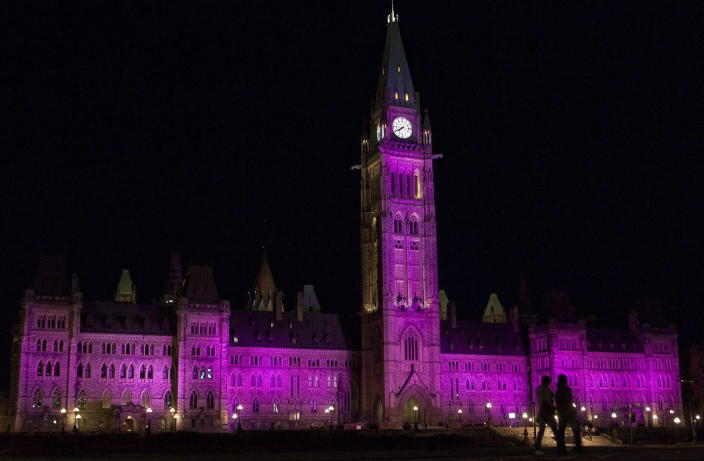 People walk past as the Parliament Buildings are lit up in pink in support of Breast Cancer awareness month in Ottawa on Thursday, Oct. 7, 2010. THE CANADIAN PRESS/Pawel Dwulit
