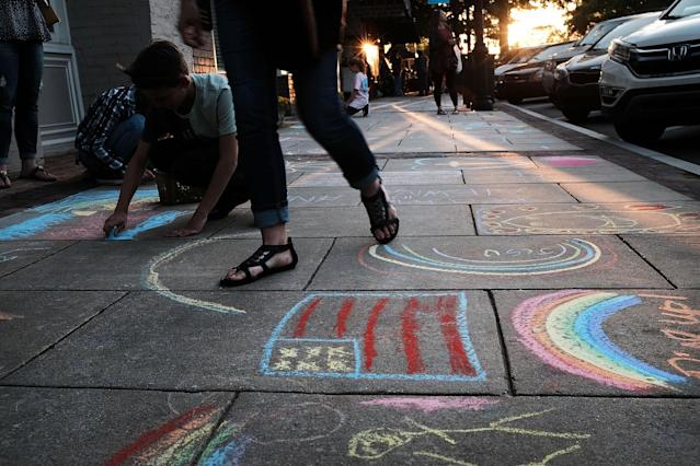 <p>Messages of racial and community unity are written in chalk throughout the streets of Newnan the night before the National Socialist Movement, one of the largest neo-Nazi groups in the US, plans to hold a rally in downtown on April 20, 2018 in Newnan, Ga. (Photo: Spencer Platt/Getty Images) </p>
