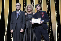 Valeria Golino, center poses with Ron Mael, left, and Russell Mael, right as they accept the award for best director on behalf of Leos Carax for the film 'Annette' during the awards ceremony for the 74th international film festival, Cannes, southern France, Saturday, July 17, 2021. (AP Photo/Vadim Ghirda)