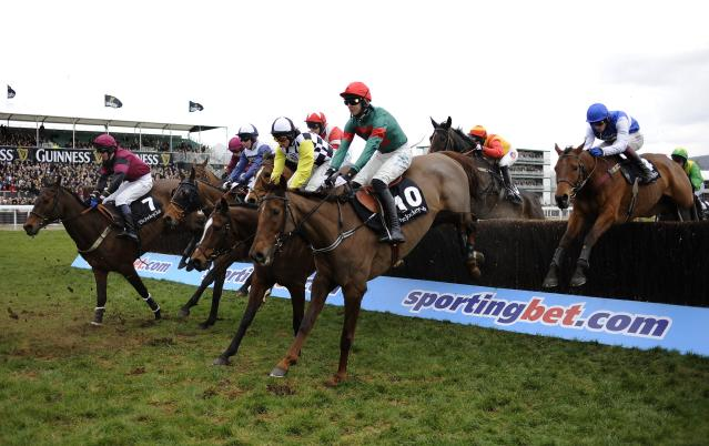CHELTENHAM, ENGLAND - MARCH 13: Runners take a fence in The John Oaksey National Hunt Steeple Chase during Ladies Day at Cheltenham racecourse on March 13, 2013 in Cheltenham, England. (Photo by Alan Crowhurst/Getty Images)
