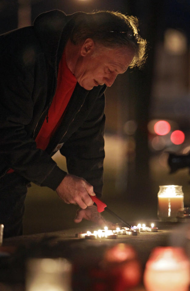 Tom Barstow re-lights candles at a makeshift memorial on the square in Chardon, Ohio Tuesday, Feb. 28. The Geauga County town east of Cleveland is mourning the death of three students and the wounding of two others in a shooting at the high school Monday morning. (AP Photo/Mark Duncan)