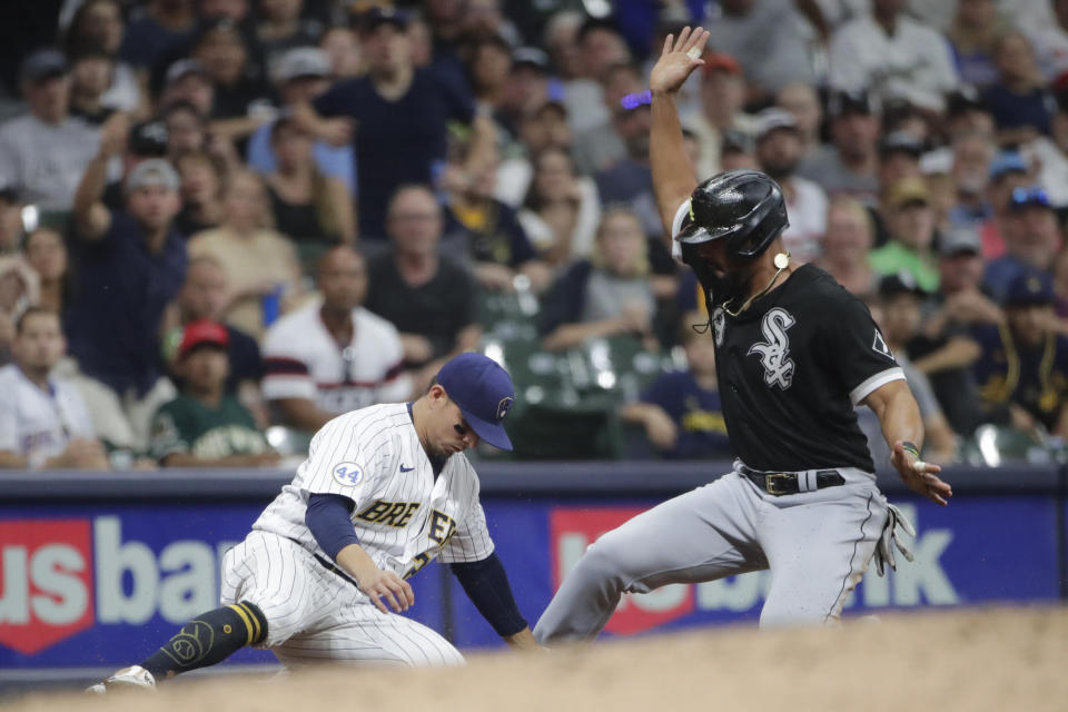 Chicago White Sox's Jose Abreu, right, slides in safely at third base past the tag of Milwaukee Brewers' Luis Urias during the sixth inning of a baseball game Friday, July 23, 2021, in Milwaukee. (AP Photo/Aaron Gash)