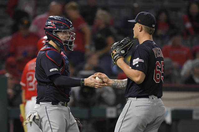 Cleveland Indians catcher Roberto Perez, left, and starting pitcher Zach Plesac congratulate each other after Los Angeles Angels' Matt Thaiss struck out to end the baseball game Tuesday, Sept. 10, 2019, in Anaheim, Calif. The Indians won 8-0. (AP Photo/Mark J. Terrill)