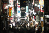 People crowd the street in the Kabukicho area, Tokyo's entertainment district, Friday, July 16, 2021, in Tokyo. Tokyo is under a fourth state of emergency, which began Monday and requires restaurants and bars to close early and not serve alcohol through the 2020 Summer Olympics, which start July 23. (AP Photo/Jae C. Hong)