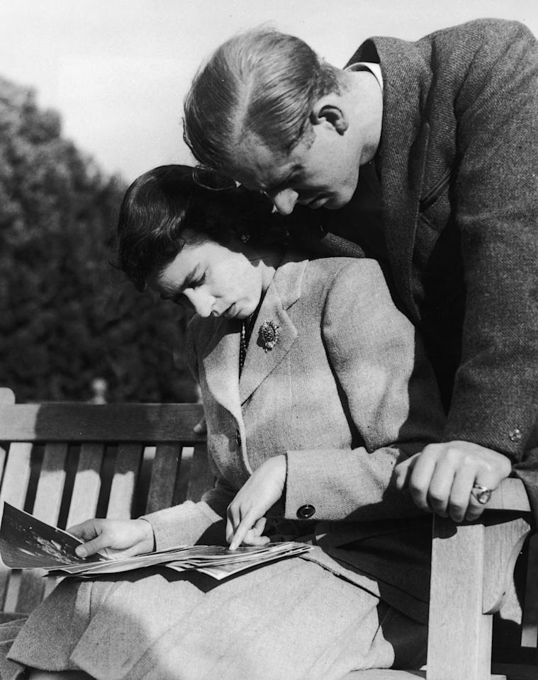 <p>Princess Elizabeth (later Queen Elizabeth II) and her husband, Philip Mountbatten, study their wedding photographs while on honeymoon in Romsey, Hampshire, November 1947. </p>