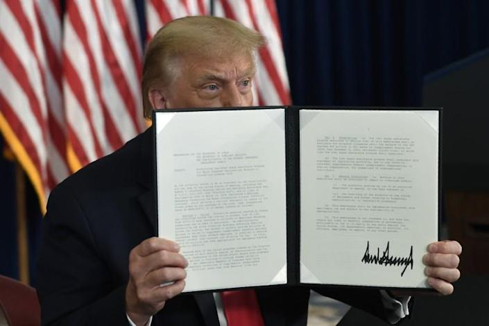 "President Trump displays one of the executive orders he signed Saturday. <span class=""copyright"">(Susan Walsh / Associated Press)</span>"