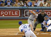 New York Mets' Omar Quintanilla, second from left, hits an RBI single as Los Angeles Dodgers starting pitcher Ricky Nolasco, left, and catcher A.J. Ellis, right, look on along with home plate umpire Chad Fairchild during the second inning of their baseball game, Monday, Aug. 12, 2013, in Los Angeles. (AP Photo/Mark J. Terrill)