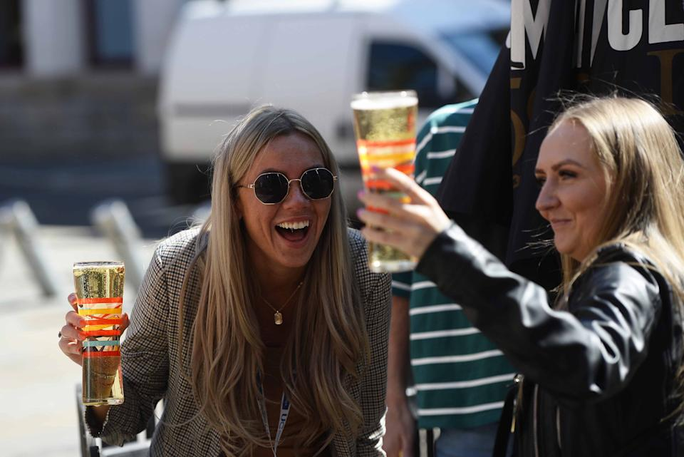 'A good news week for the UK': People enjoy a drink in Belfast on Friday. (PA)